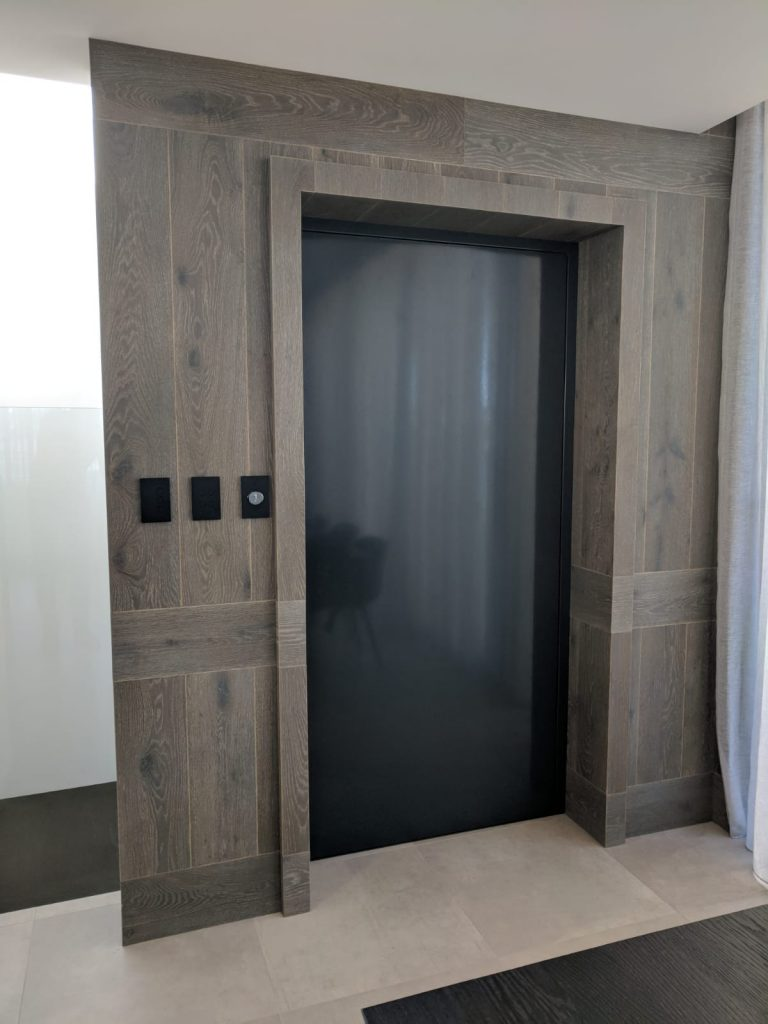classic home lift built into feature wall with dark reflective door