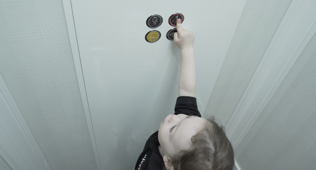 a child is in a cream coloured elevator. the child presses the level one button.