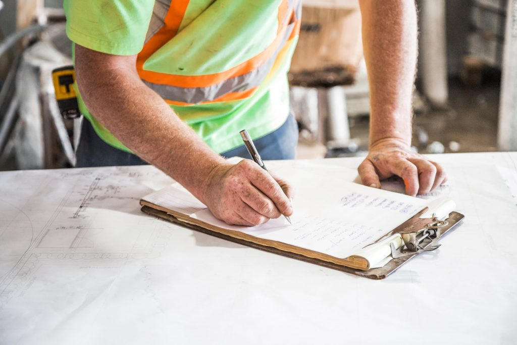 a workman in a hi-vis shirt writes on a project sheet in a worksite.