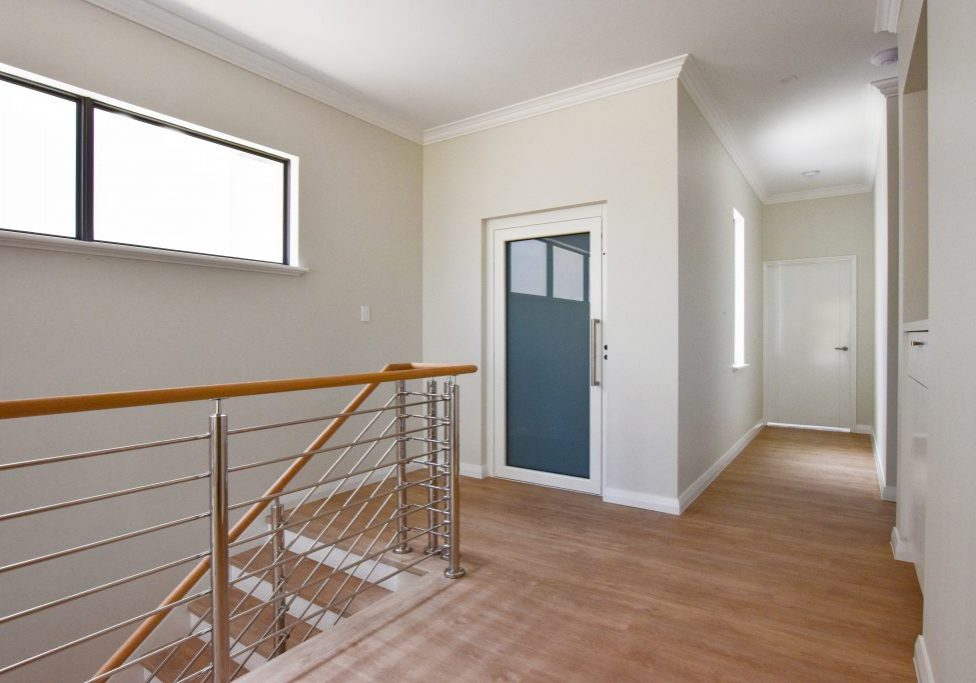 Residential lift with white framed door in Applecross. Located next to stairs.
