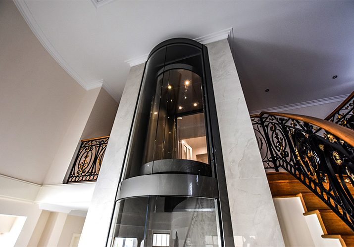 matte black and glass round home lift adjacent to spiral staircase