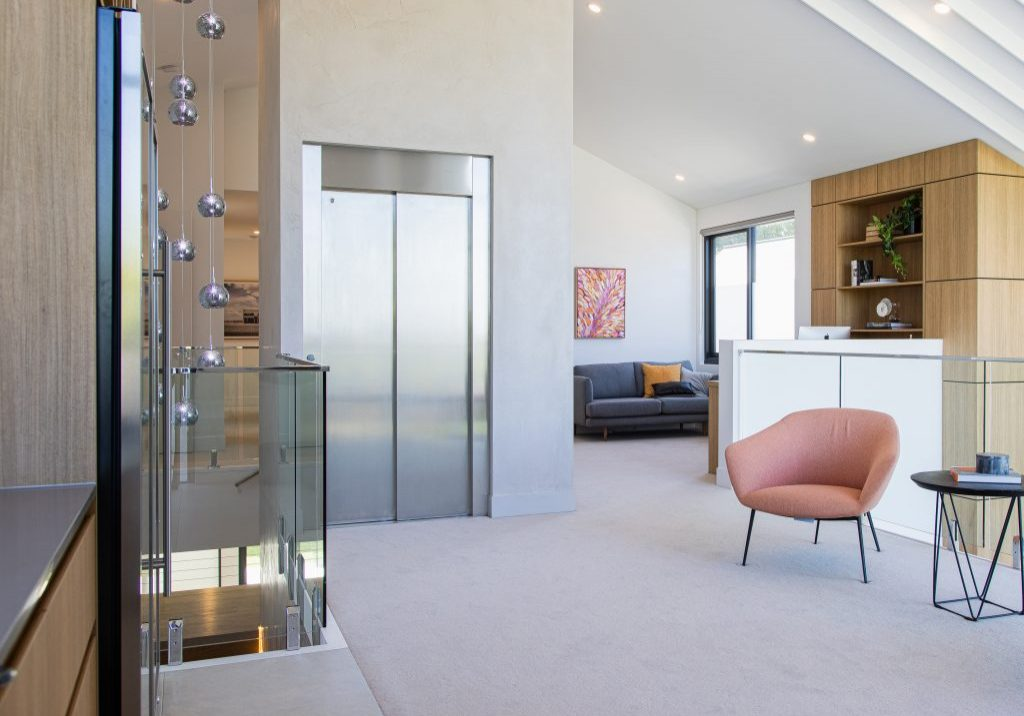 minimalist stainless steel home lift installed in upper living area