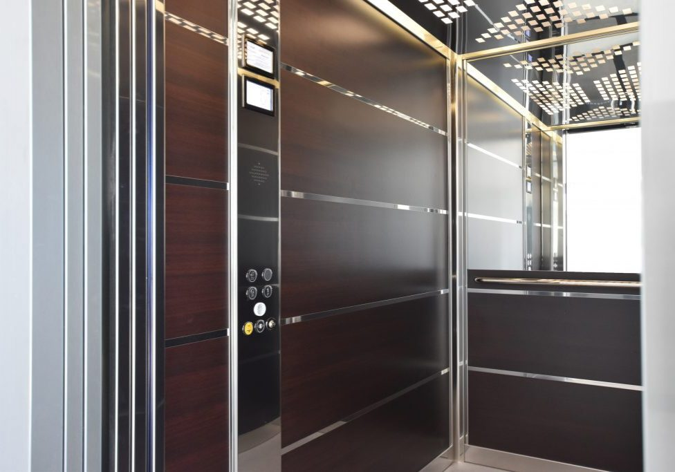 large lift cabin with dark wood panels, mirrored details and designer lights